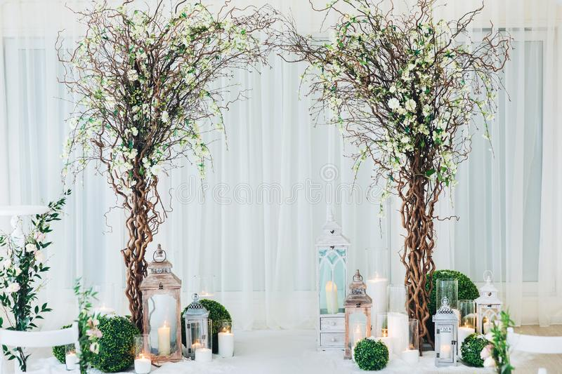 Indoor wedding ceremony with white wedding arch decorated with flowers and big white candles.  stock photo