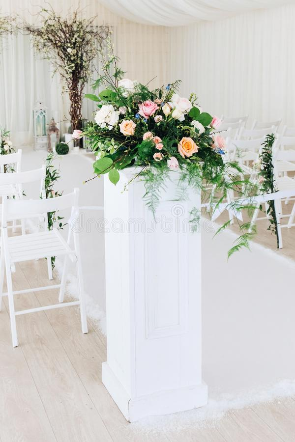 Indoor wedding ceremony with white wedding arch decorated with flowers and big white candles.  stock photography