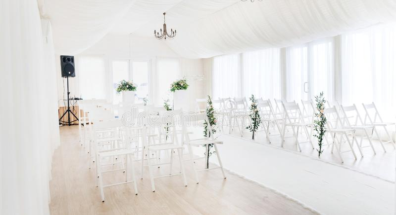 Indoor wedding ceremony with white wedding arch decorated with flowers and big white candles. General plan of the room on wide angle. Indoor wedding ceremony stock photography