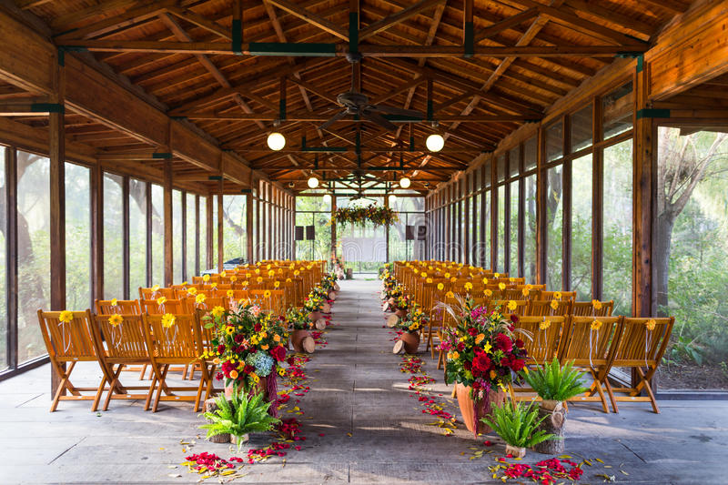 Indoor wedding Scene. Chairs and flowers at an indoor wedding party royalty free stock photo