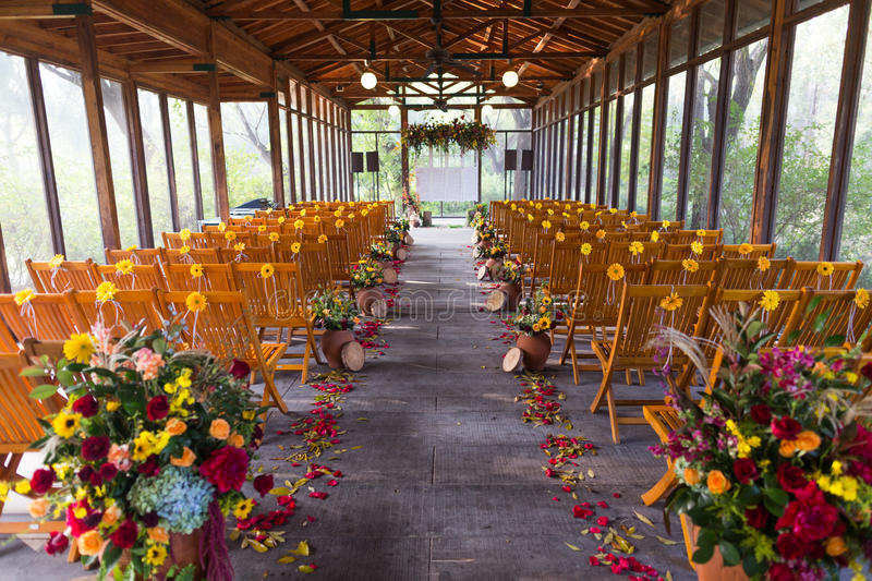Indoor wedding Scene. Chairs and flowers at an indoor wedding party royalty free stock image