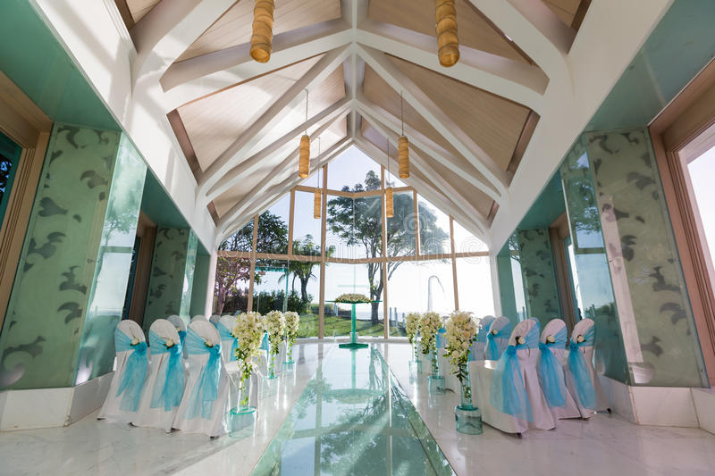 Indoor wedding Scene. Chairs and flowers at a indoor wedding party at seaside stock image