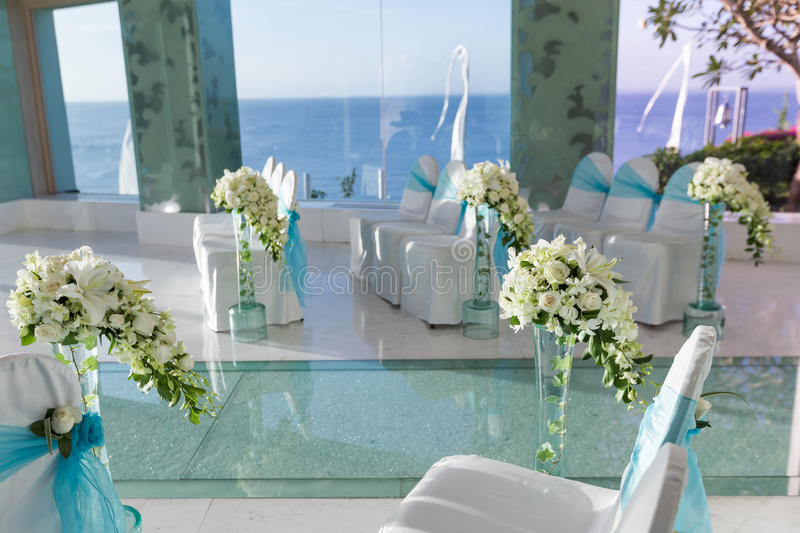 Indoor wedding Scene. Chairs and flowers at a indoor wedding party at seaside royalty free stock photo