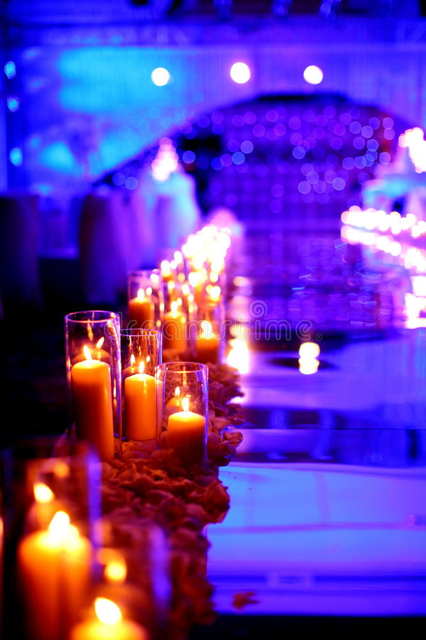Indoor wedding Scene. Flowers and candles at an indoor wedding stock image