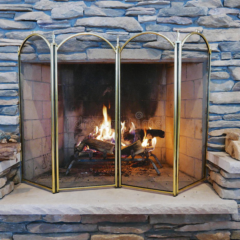 Indoor Wood Burning Stone Fireplace. A wood fire burning in an indoor stone fireplace with a metal mesh safety screen royalty free stock photos