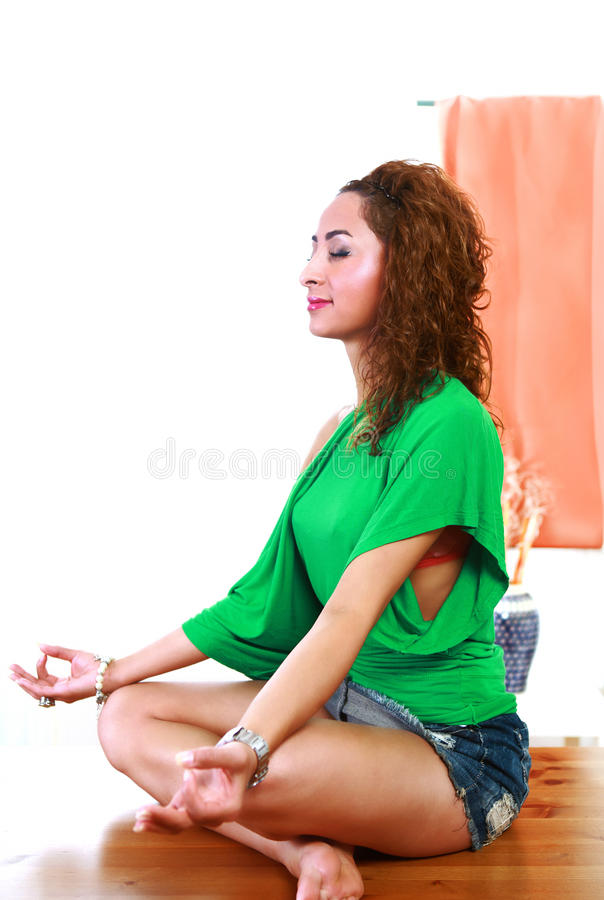 Indoor yoga. Practice with pretty young woman in lotus pose royalty free stock photography