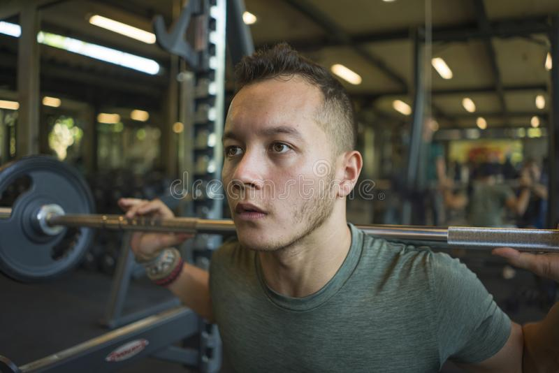 Indoors fitness portrait of young athletic and sweaty mixed ethnicity man doing squats with barbell bodybuilding hard with royalty free stock images