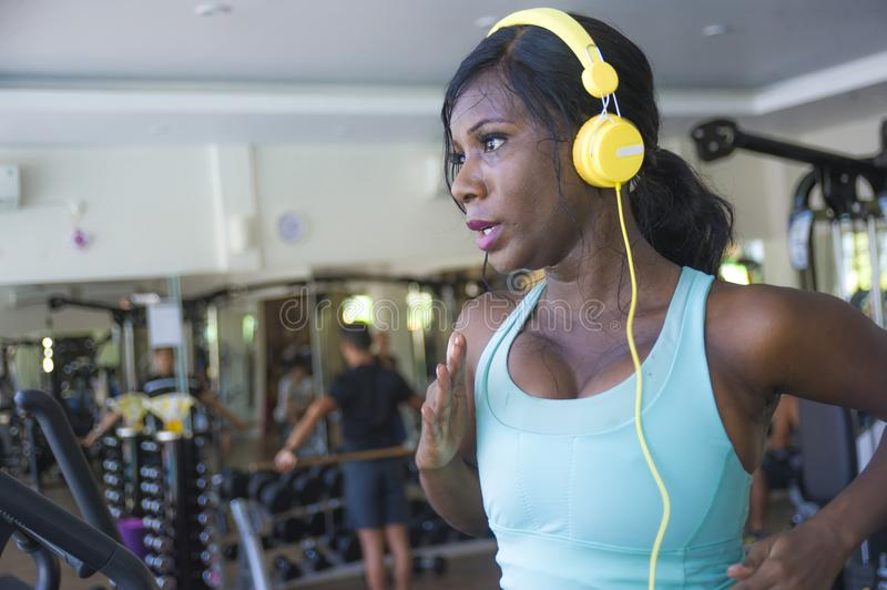 Indoors gym portrait of young attractive black afro American woman with headphones training hard all sweaty at fitness club a trea. Dmill running workout in body stock photos