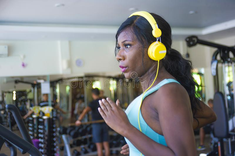 Indoors gym portrait of young attractive black afro American woman with headphones training hard all sweaty at fitness club a trea. Dmill running workout in body royalty free stock images