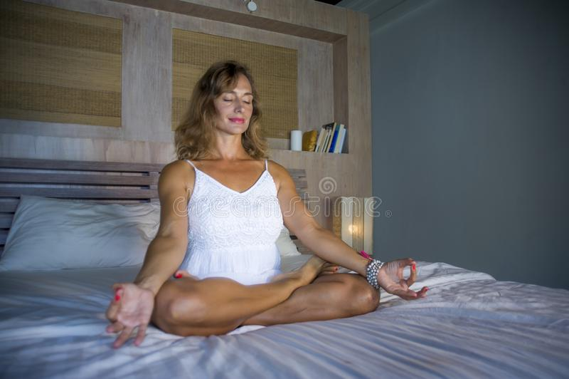 Indoors portrait of beautiful and fit healthy woman 30s practicing yoga in bed posing calm and relaxed concentrated in meditation. Exercise in mind control and royalty free stock images