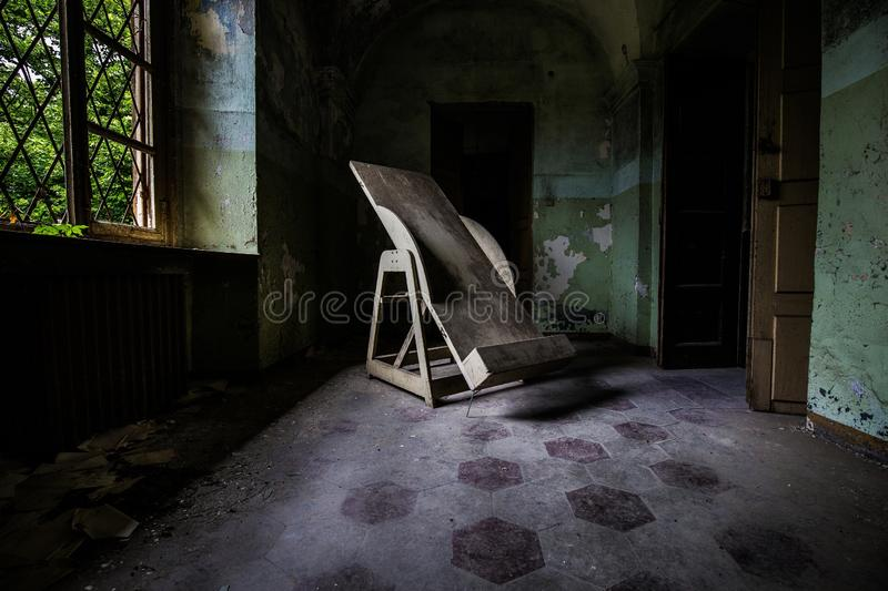 Indoors shot of an abandoned hospital corridor with an old Trendelenburg table in the corridor stock photography