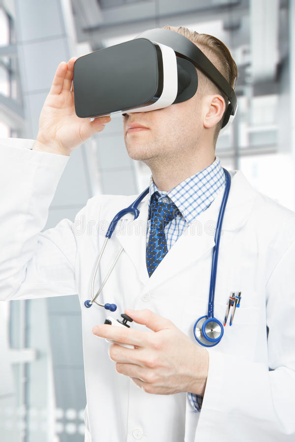 Indoors shot of male doctor wearing VR glasses stock photography