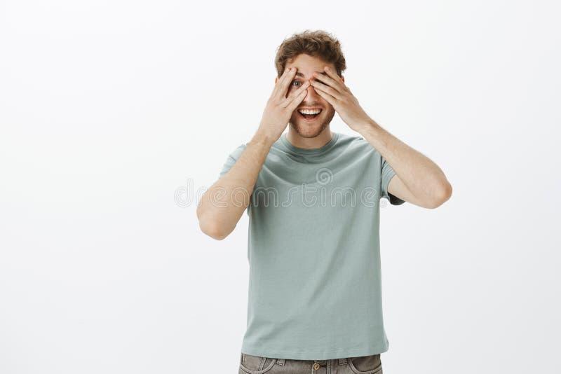 Indor ha sparato del modello maschio maturo felice allegro in maglietta, coprendo osserva con le palme e dare una occhiata tramit immagini stock libere da diritti
