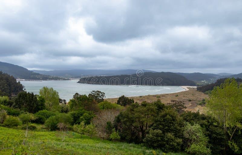 Indrukwekkend landschap van een strand dat door bos met verschillende en kleurrijke bomen in een Coruña, Galicië, Spanje wordt o stock foto