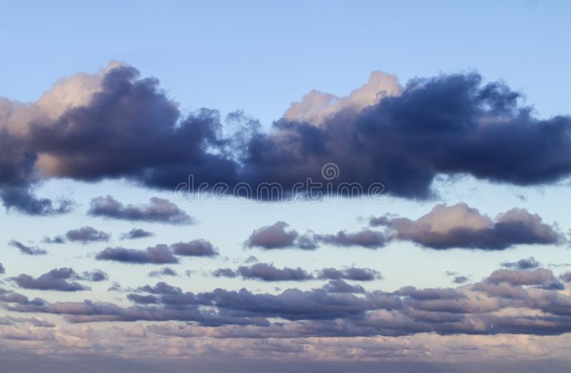 Indrukwekkende die hemel bij zonsondergang met lagen wolken met roze worden getint die neer naar de horizon hellen stock afbeeldingen