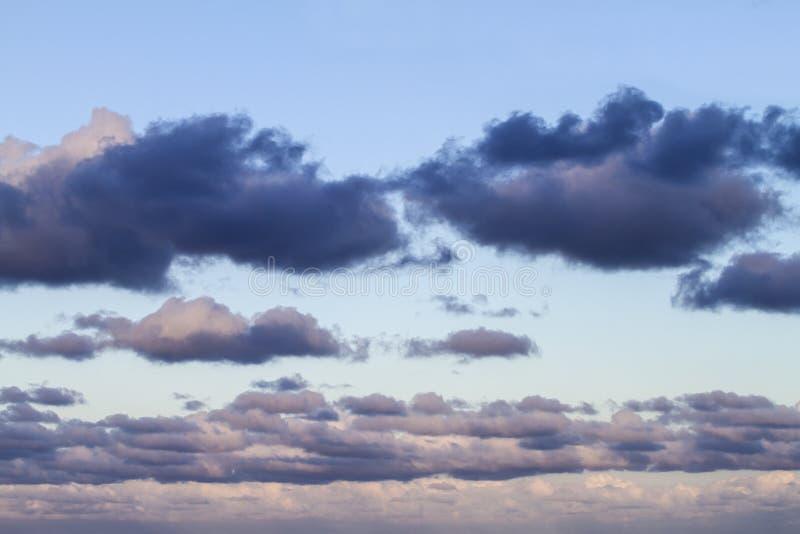 Indrukwekkende die hemel bij zonsondergang met lagen wolken met roze worden getint die neer naar de horizon hellen stock fotografie