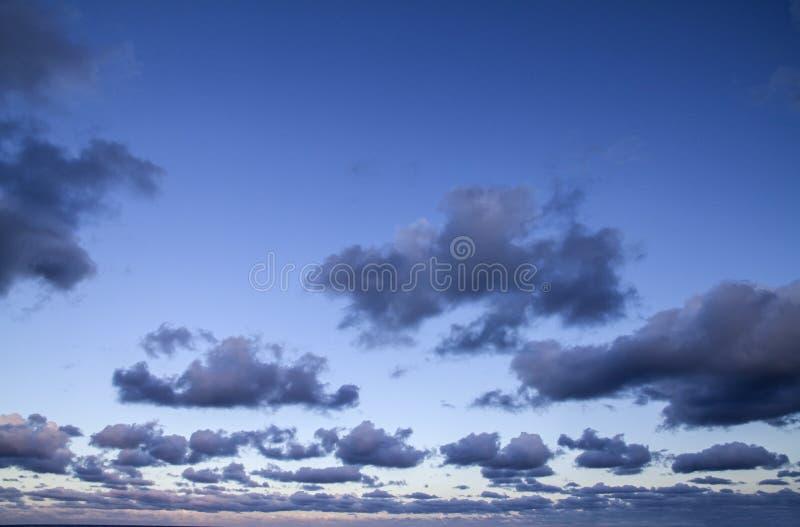 Indrukwekkende die hemel bij zonsondergang met lagen wolken met roze worden getint die neer naar de horizon hellen royalty-vrije stock foto