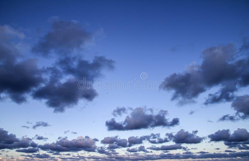 Indrukwekkende die hemel bij zonsondergang met lagen wolken met roze worden getint die neer naar de horizon hellen stock foto's