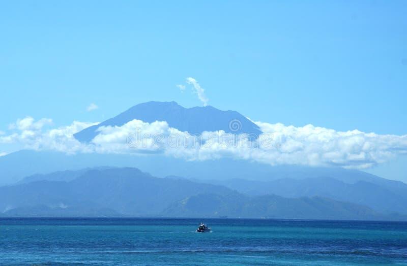 Indrukwekkende vulkaan boven de oceaan stock foto