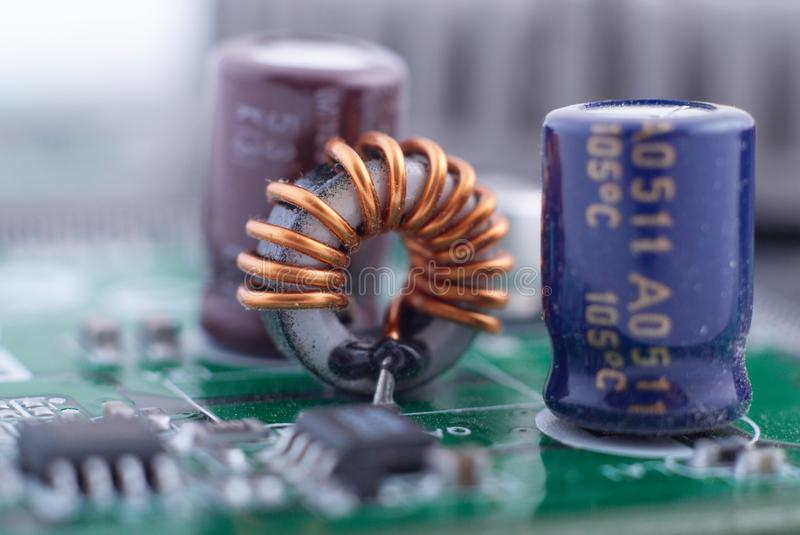 Inductor with motherboard background. Computer board chip circuit. Microelectronics hardware concept. stock photography