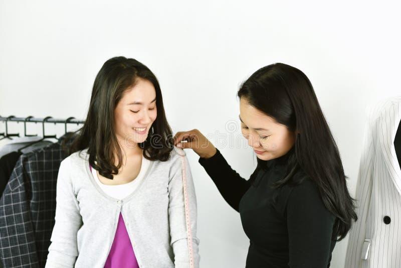 Indumento di fabbricazione e di misura del progettista del sarto da donna sul corpo del cliente immagine stock