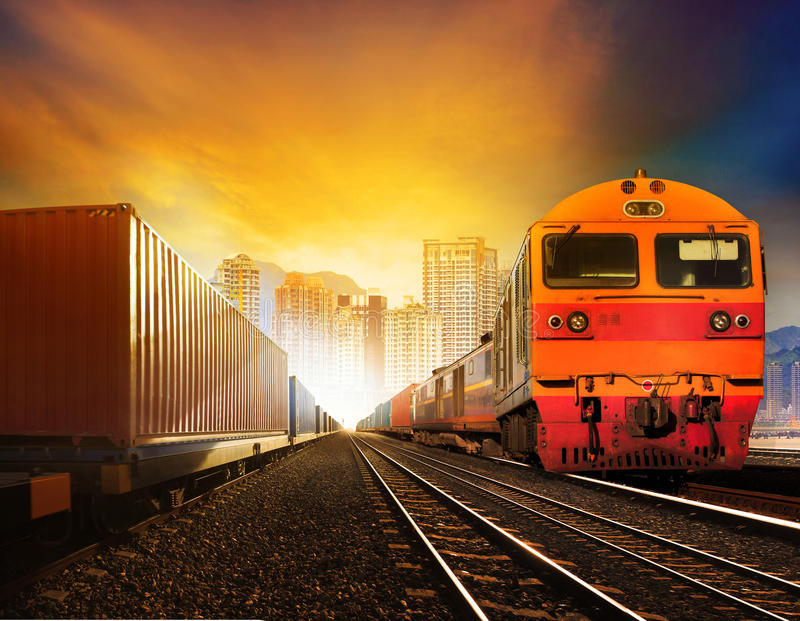 Industindustries container trainst and boxcar on track. Industries container trainst and boxcar on track against building in town background for industrial stock image