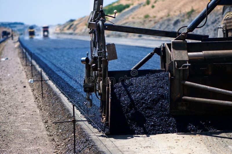 Industriële bestratingsvrachtwagen die vers asfalt leggen royalty-vrije stock afbeelding
