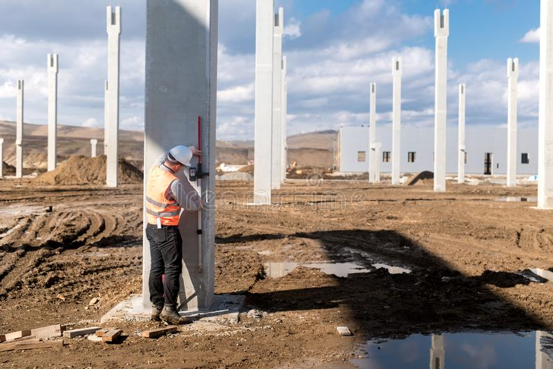 Industriële civiel-ingenieur die aan bouwwerf werken Professionele landmeter die niveau meten stock afbeeldingen