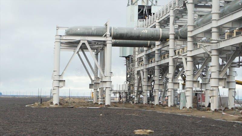 Industriële die pijpleiding dichtbij kust wordt gebouwd Grote olieraffinaderij dichtbij het overzees in een bewolkte ochtend Olie royalty-vrije stock afbeeldingen