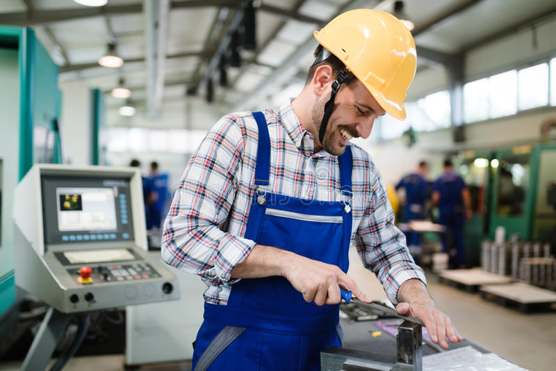 Industriële fabriekswerknemer die in metaal verwerkende industrie werken stock foto's