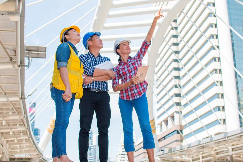 Industriële ingenieur drie die en zich aan de veiligheidshelm van de rechterkantslijtage bevinden kijken met holdingsinspectie en royalty-vrije stock fotografie