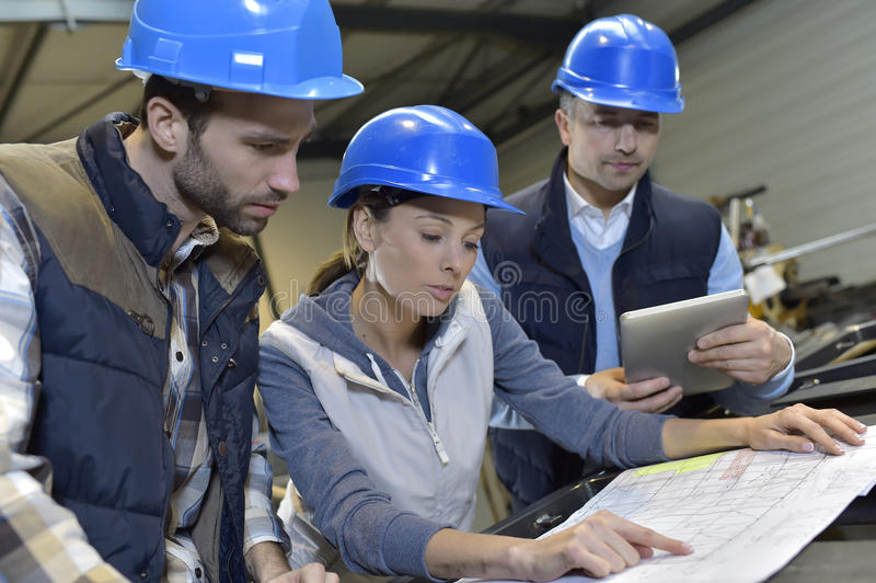 Industriële ingenieurs die en in mechanische fabriek samenkomen bespreken royalty-vrije stock foto's