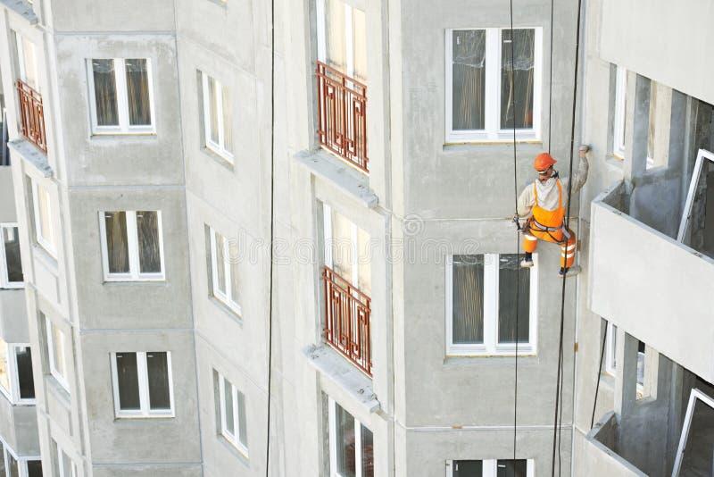 Industriële Klimmer Bouwer die de buitenvoorgevel verbindingen van de de bouwnaad met isolatiemastiek verzegelt royalty-vrije stock afbeelding