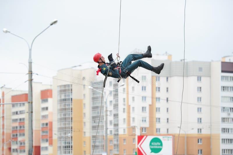 Industriële klimmer in helm en eenvormig Gewaagde baan Het extreme werk stock foto