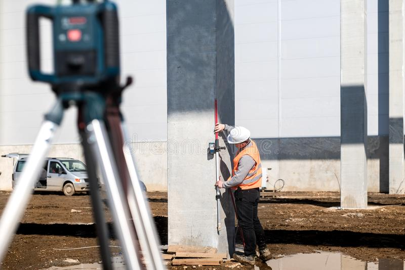 Industriële landmeter op bouwwerf, die met thodolite, gps systeem en niveaumachine werken stock afbeeldingen