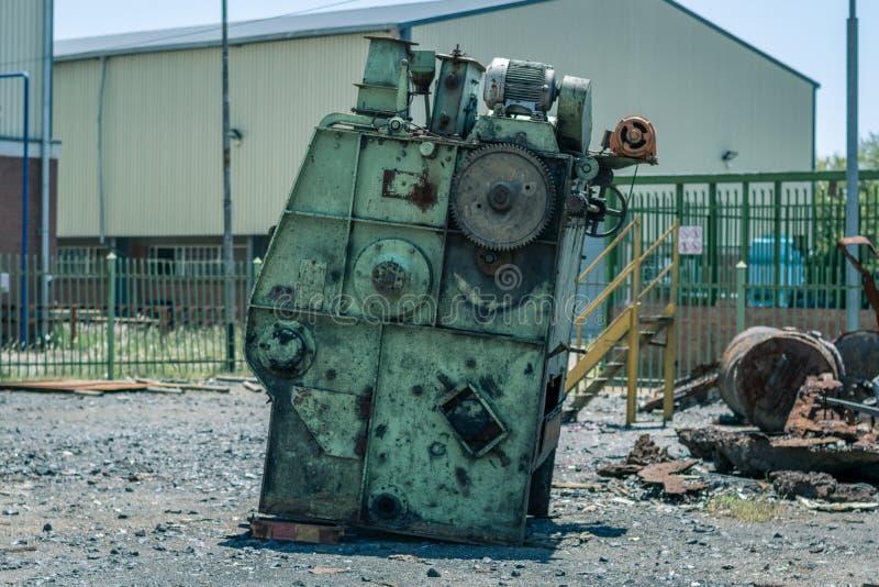 Industriële machinesschroot in een lege werf stock fotografie