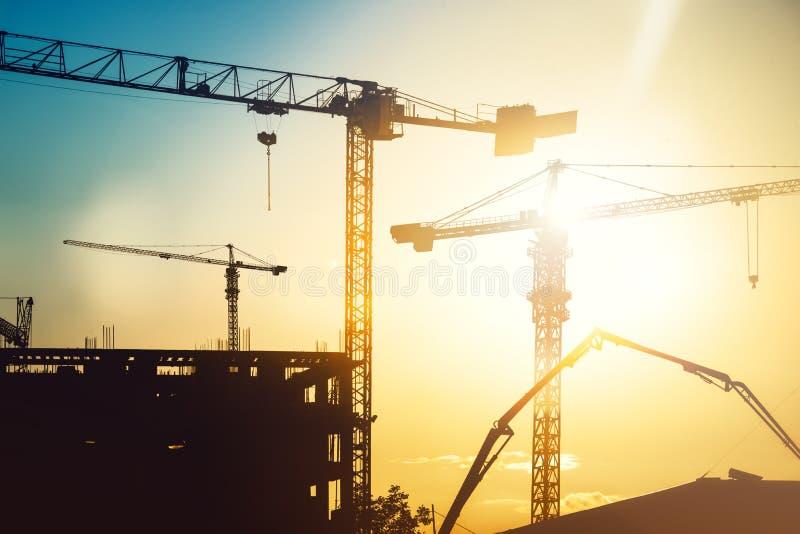Industriële op zwaar werk berekende bouwwerf met torenkranen en de bouwsilhouetten stock afbeeldingen