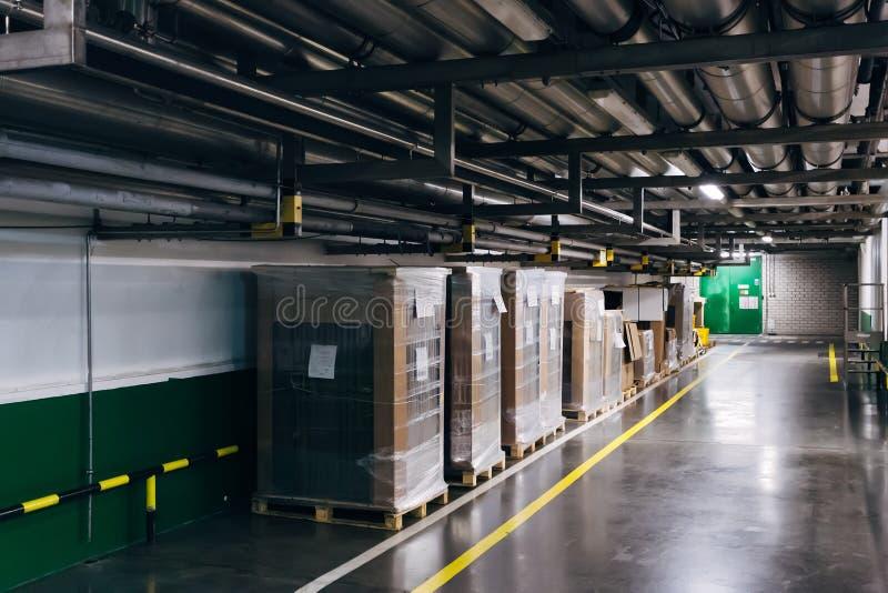 Industriële pakhuisgang Goederen in karton en polyethyleen verpakking stock foto's
