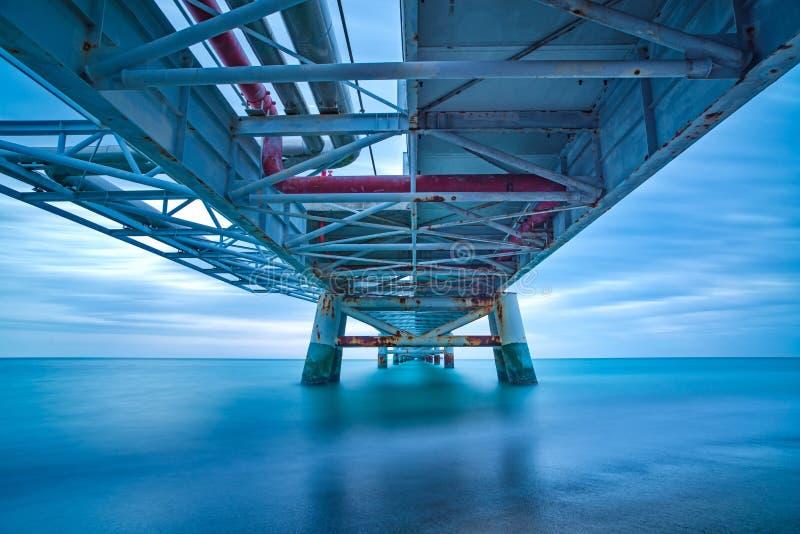 Industriële pijler op het overzees. Bodemmening. Lange blootstellingsfotografie. stock foto's
