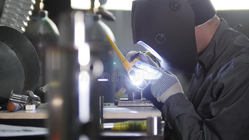 Industriële productie Zijaanzicht die van mannelijke lasser, donkere werkkledij, bouwhandschoenen dragen en masker lassen royalty-vrije stock fotografie