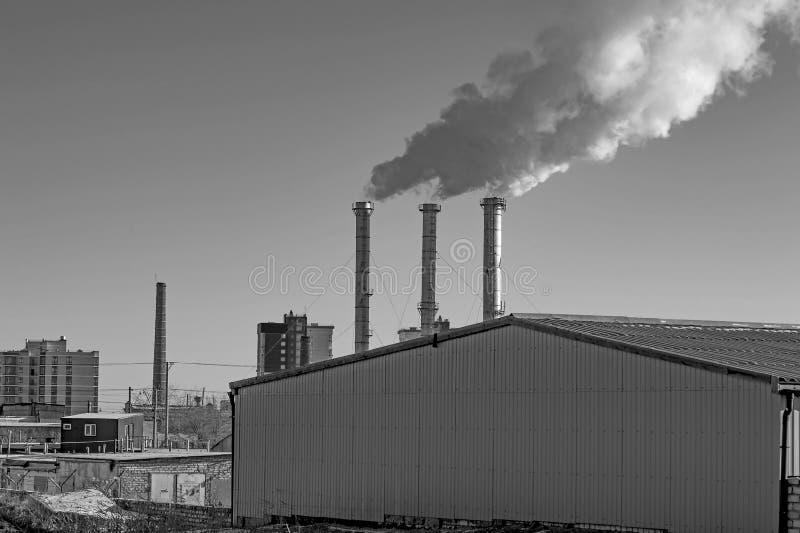 Industriële rook van schoorsteen op hemel Zwart-wit beeld stock afbeelding
