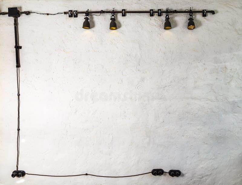 Industriële tegenhangerlampen tegen ruwe muur, zolderstijl de zwarte draden en de contactdozen rond de perimeter leiden tot een k royalty-vrije stock afbeeldingen