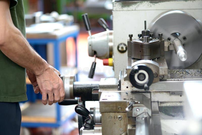 Industri- arbetare som gör manuellt arbete med en drejbänk royaltyfria bilder