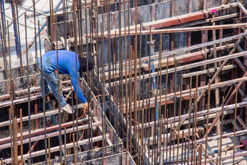 Industri?le lassenarbeider voor de bouw van het staalwerk in de gebiedsbouw met Lassenproc?d? door Beschermd MetaalBooglassen stock foto's