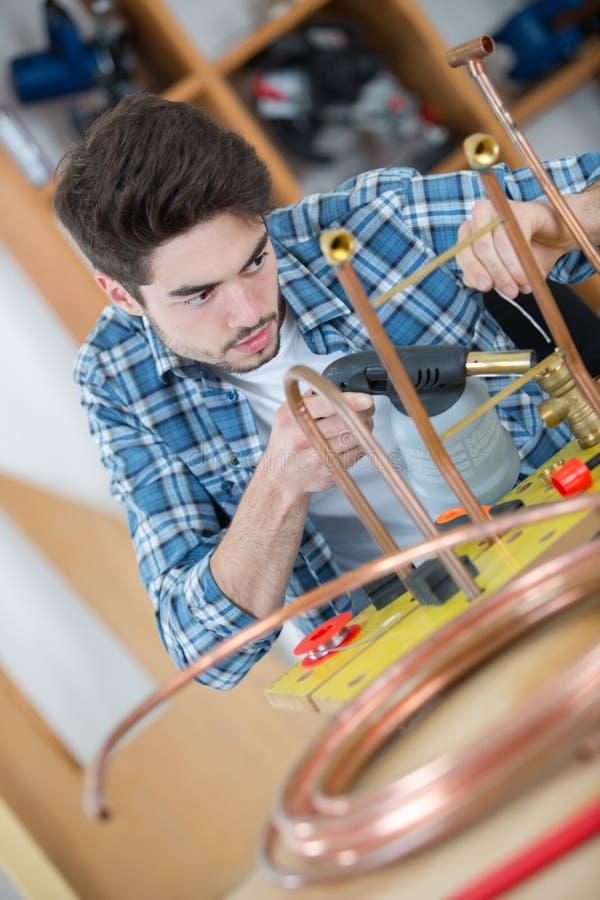 Industri?le loodgieter die soldeerlamp gebruiken stock foto
