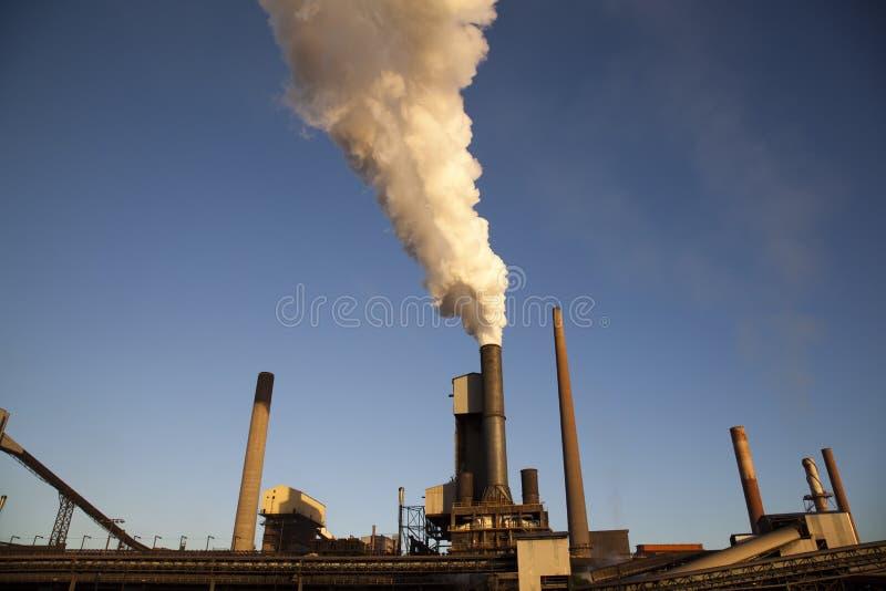 Industria de acero - humo que se levanta de molino imagen de archivo