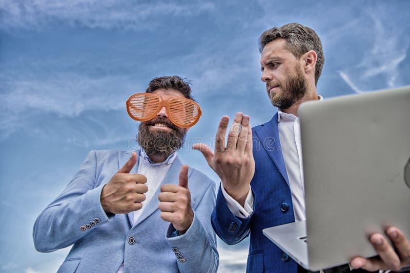 Industria della gestione di evento Comportamento non professionale Uomo d'affari con il computer portatile serio mentre socio com immagine stock libera da diritti