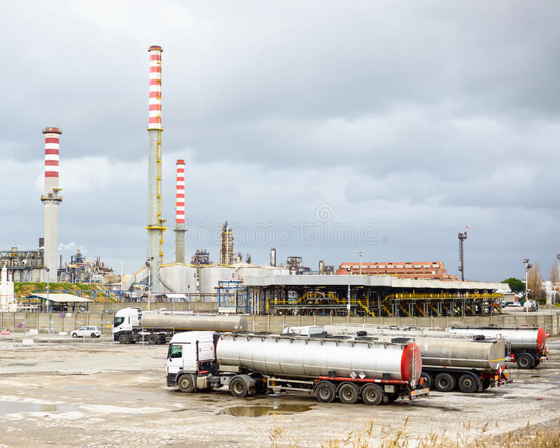 Industria della raffineria di petrolio, fumaioli e camion o camion dell'autocisterna immagini stock libere da diritti