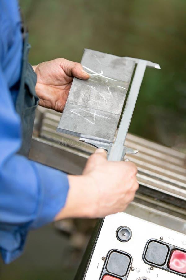 Industria metalúrgica: detalle de medición del trabajador con pinza de freno imagen de archivo libre de regalías