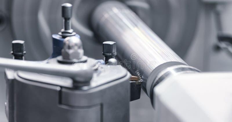 Industria metallurgica: asse d'acciaio del metallo di taglio che elabora sulla macchina del tornio in officina Fuoco selettivo su fotografia stock